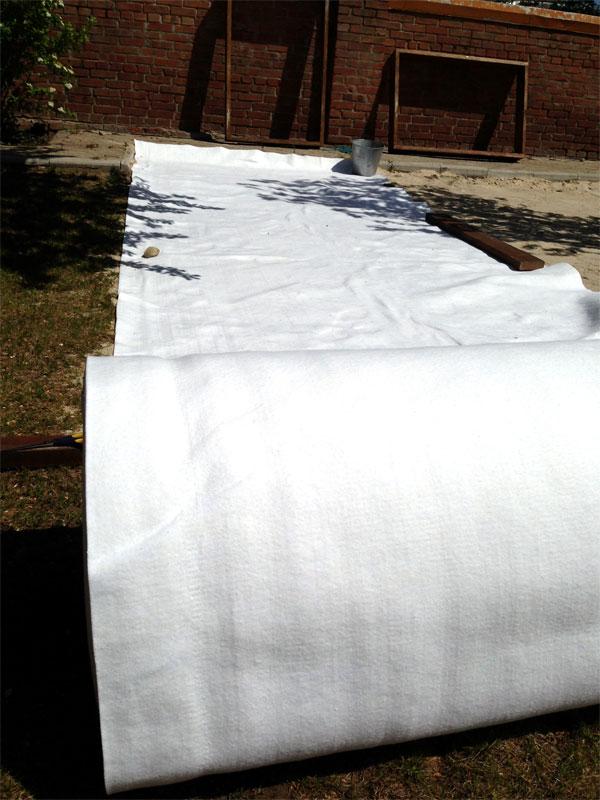 Раскладываем рулон геотекстиля по площади огорода