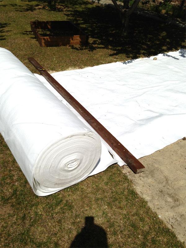 Раскладка рулона геотекстиля в огороде